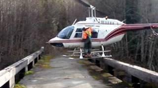 ヘリコプターが橋の手すりに着地して人を降ろす。