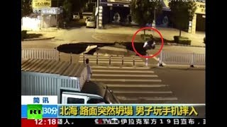 RAW: Motorcyclist plunges into sinkhole in China while fiddling with his phone - RUSSIATODAY