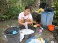 Beautiful young filipina girl washing clothes by hand in Philippine province