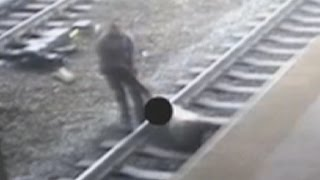 Man fights to stay on tracks as train roars in - CNN