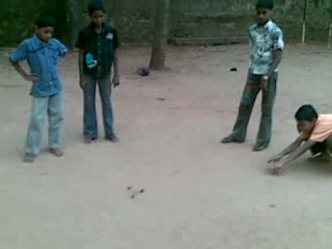 indian boys playing goli (famous in kanyakumari) koli viliyaduthal