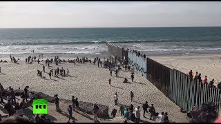 Dozens of migrants climb border fence near Tijuana, Mexico - RUSSIATODAY