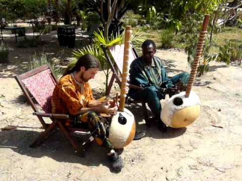 Jali Sherrifo Konteh plays Kora with a student at Gunjur Project Lodge, The Gambia