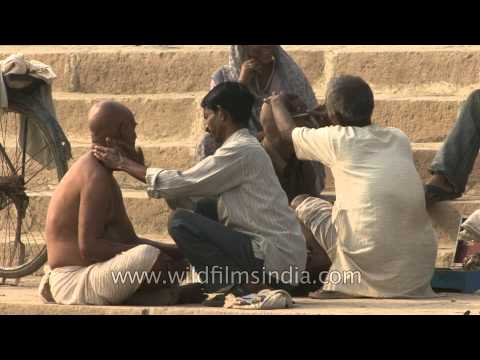 Men getting their heads shaved on the ghat along the Ganga