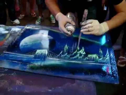 Artista callejero pintando arte en cartulina usando solo spray aerosol.
