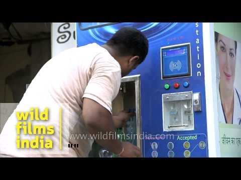 Residents fill bottles with pure drinking water from Swajal machine