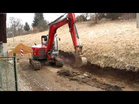Bagr tahá z cesty ocelové roury. Excavator pulls steel pipes from the road..wmv