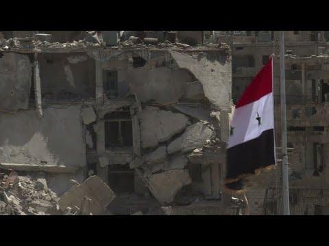 قوات النظام ترفع العلم السوري في حي الحجر الاسود