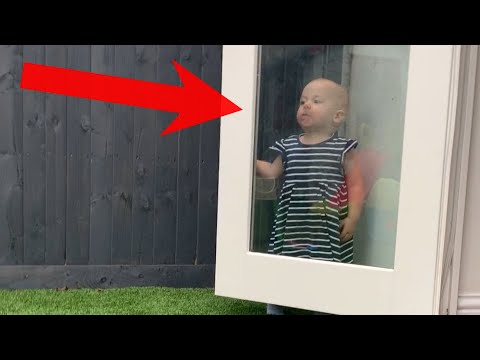 Adorable Little Girl Stands Behind Glass Door In Hide-And-Seek Fail