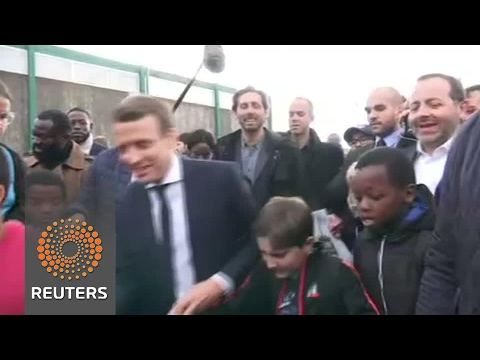 Macron kicks a ball about with young people in Paris suburb